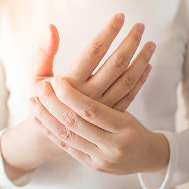 手・肘の痛みに悩む女性