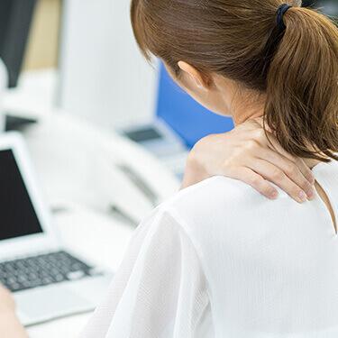 首・肩の痛みに悩む女性